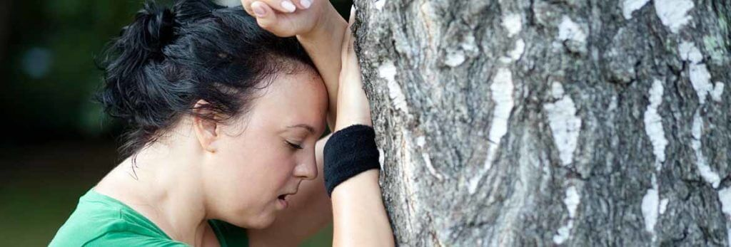 tired woman leaning on tree